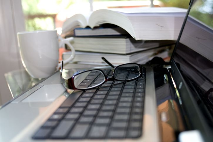 computer-keyboard-atop-which-a-pair-of-reading-glasses-725x482