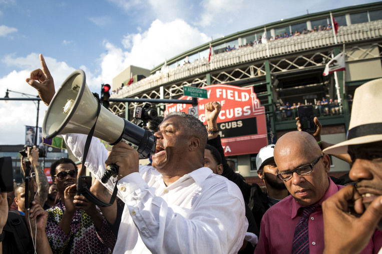 Rev. Gregory Seal Livingston, center, leads an anti-violence rally outside Wrigley Field, shortly before a Chicago Cubs baseball game, after marching and shutting down Lake Shore Drive, Thursday, Aug. 2, 2018, in Chicago. (Ashlee Rezin/Chicago Sun-Times via AP) ORG XMIT: ILCHS504